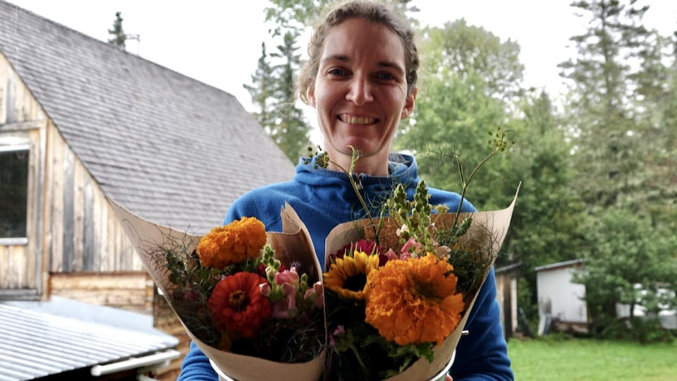 Geneviève Larivière est photographiée avec des bouquets à la main.
