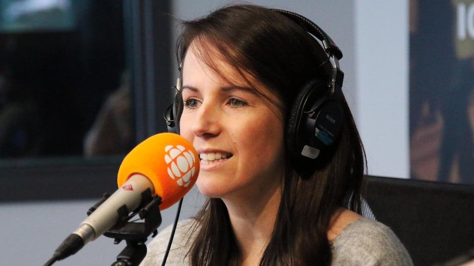 Geneviève O'Gleman devant un micro dans le studio d'ICI Québec.