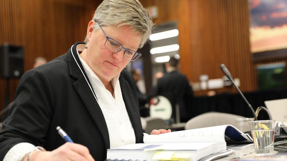 Une femme prend des notes en consultant le document budgétaire.