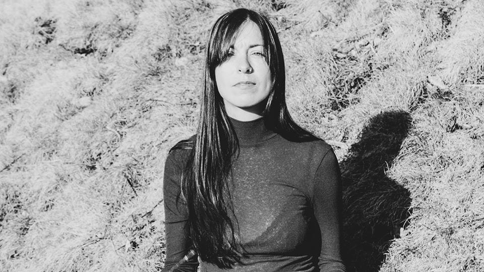Une photo en noir et blanc d'une femme assise dans le gazon