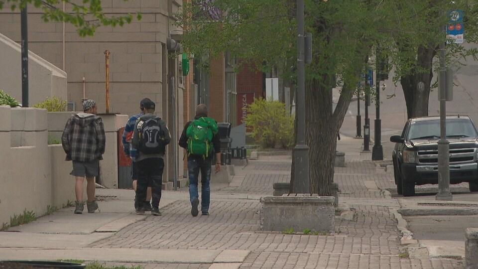 Des passants marchent sur la rue Racine.