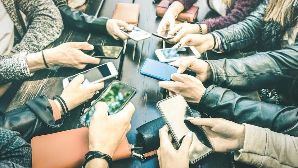 Des gens, réunis autour d'une table, partagent des contenus à l'aide de leur téléphone intelligent.