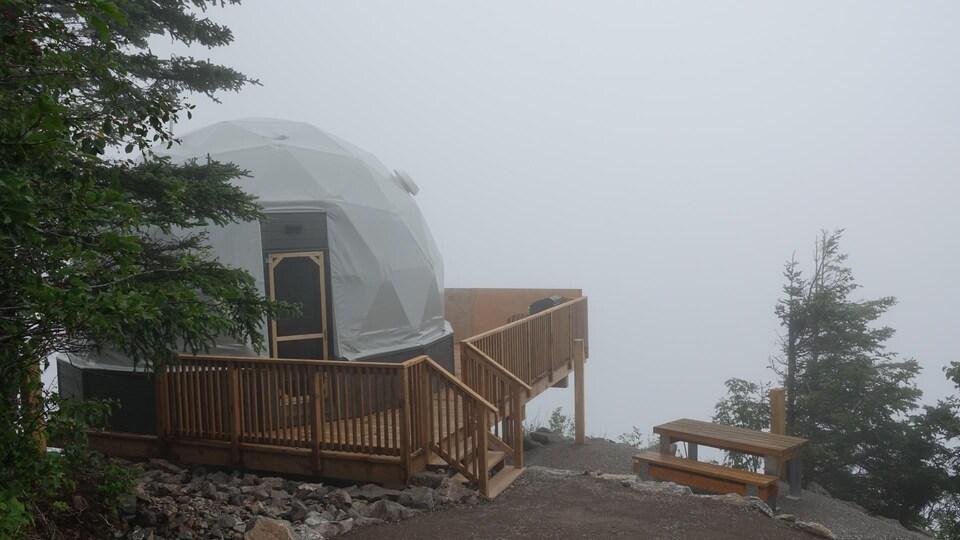 Un géodôme dans un décor de brouillard.