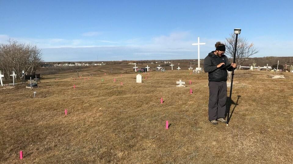 Un technicien tenant un géoradar se trouve sur un vaste terrain. Des croix y sont érigées ainsi que de petits piquets roses.