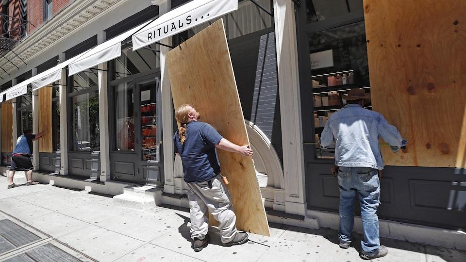 Des employés posent des feuilles de contreplaqué contre de grandes fenêtres donnant sur une rue.
