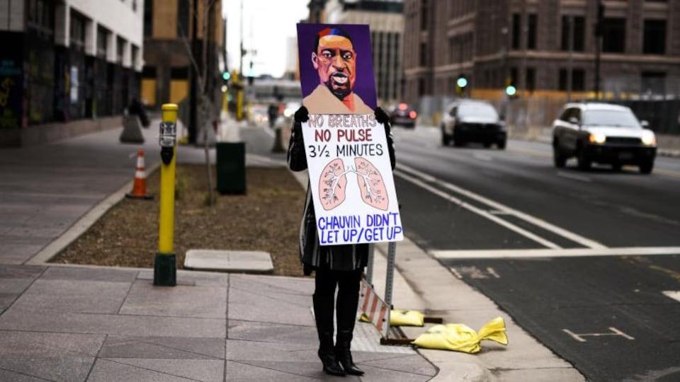 Une personne tient une pancarte où est illustré le portrait de George Floyd et des poumons.