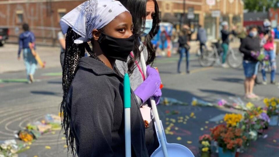 Deux femmes, tenant un balai à la main, et portant un masque.