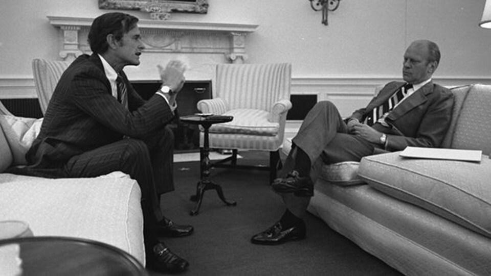 Gerald Ford et George H. W. Bush sont assis l'un devant l'autre dans le bureau ovale.