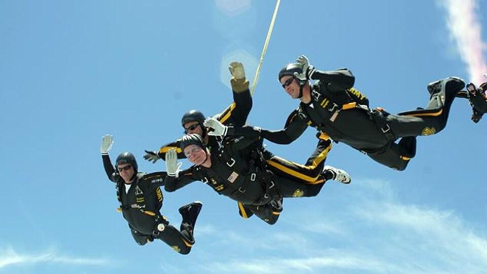 George H. W. Bush est entouré de quatre parachutistes en pleine descendante.