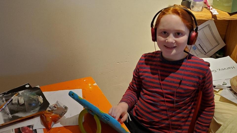 George Harvey souriant porte des écouteurs et est assis à une petite table orange devant un écran tactile.