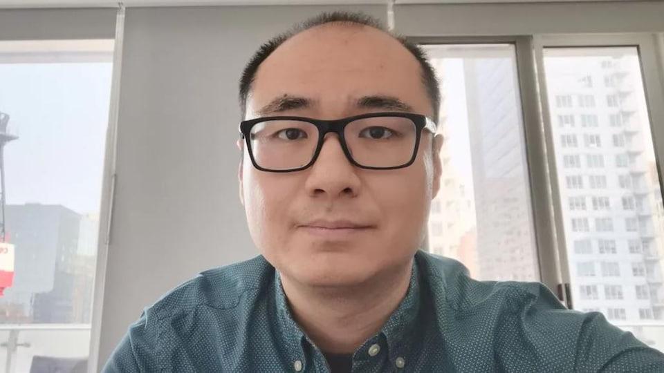 Un homme portant des lunettes, dans un bureau.
