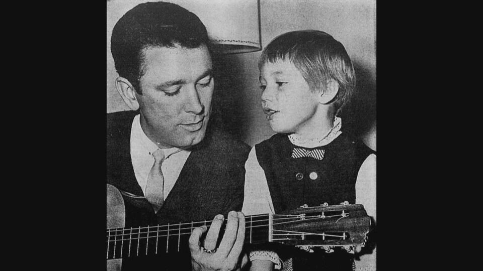 Le chanteur Georges La Flèche joue de la guitare à côté d'un enfant.