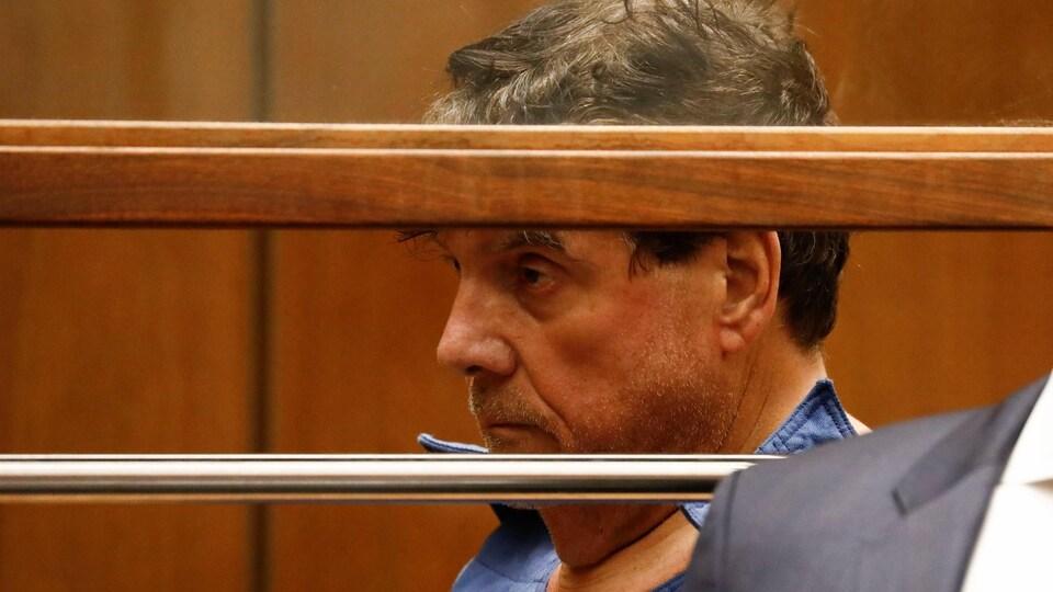 L'homme apparaît derrière des barreaux, dans une salle d'audience.