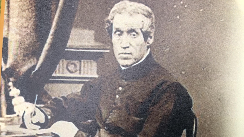 Une photo noir et blanc de l'abbé Georges-Antoine Belcourt, assis à un secrétaire.