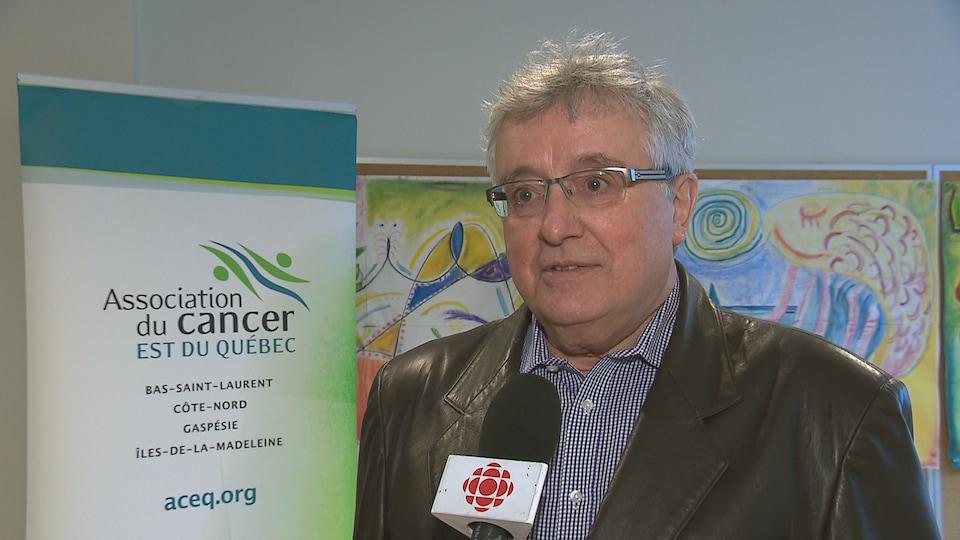 Dr Georges Levesque, l'un des administrateur de l'Association du cancer de l'est du Québec pose devant une pancarte de l'association.