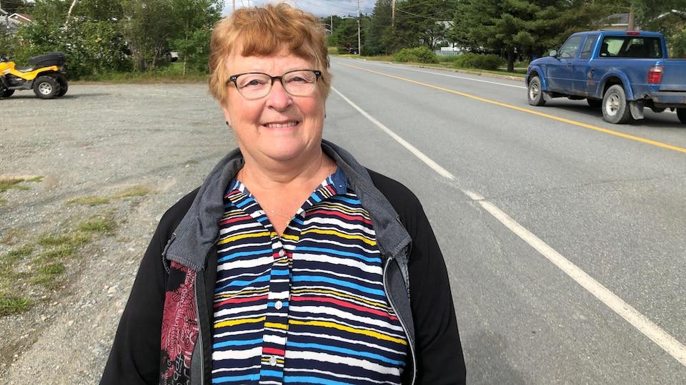 Une femme sourit à la caméra au bord d'une rue résidentielle.