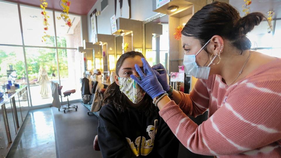 La jeune fille est assise et porte un masque, pendant que l'esthéticienne, qui porte aussi un masque travaille son sourcil avec une pince.