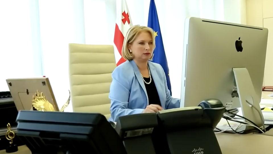 Natia Turnava assise devant des écrans d'ordinateurs et des téléphones.