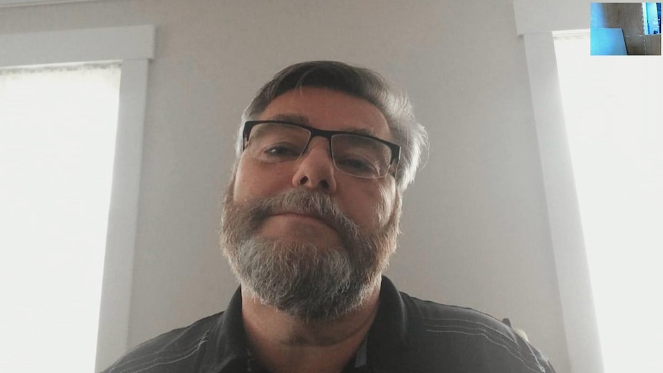 Un homme en entrevue par webcam.
