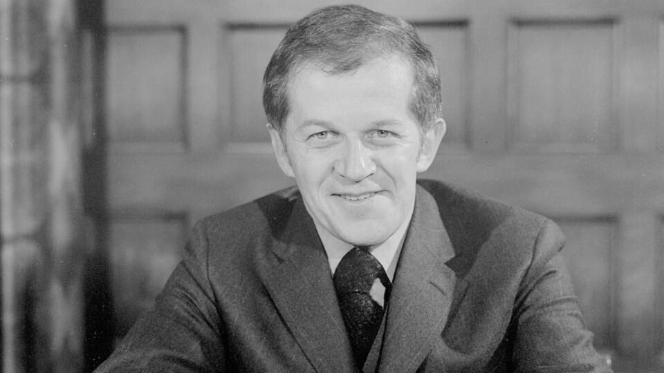 Gérard Lebel, souriant et assis à un bureau lors d'une séance de photographie officielle.