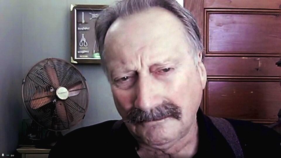 Un homme devant un webcam. Un ventilateur en métal est placé derrière lui.