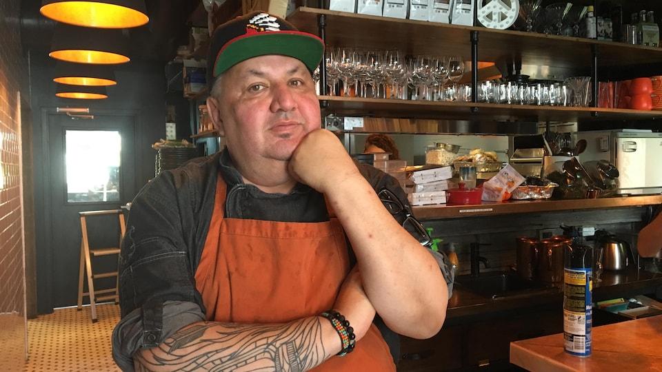 Un homme d'origine autochtone, portant un tablier et une casquette, pose dans son restaurant.