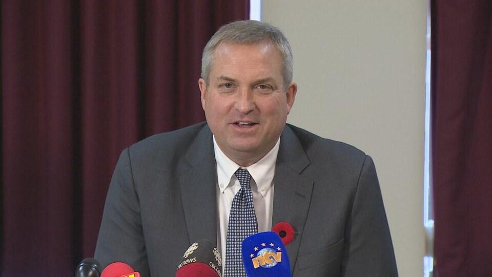 Gerry Byrne assis devant des micros lors d'une conférence de presse.