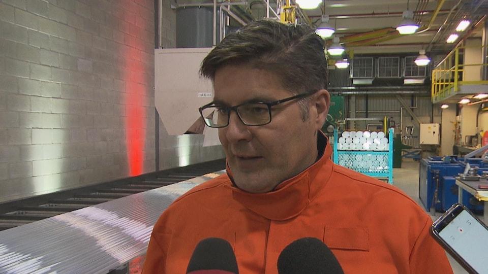 Gervais Jacques se trouve devant quelques microphones dans une usine de Rio Tinto.