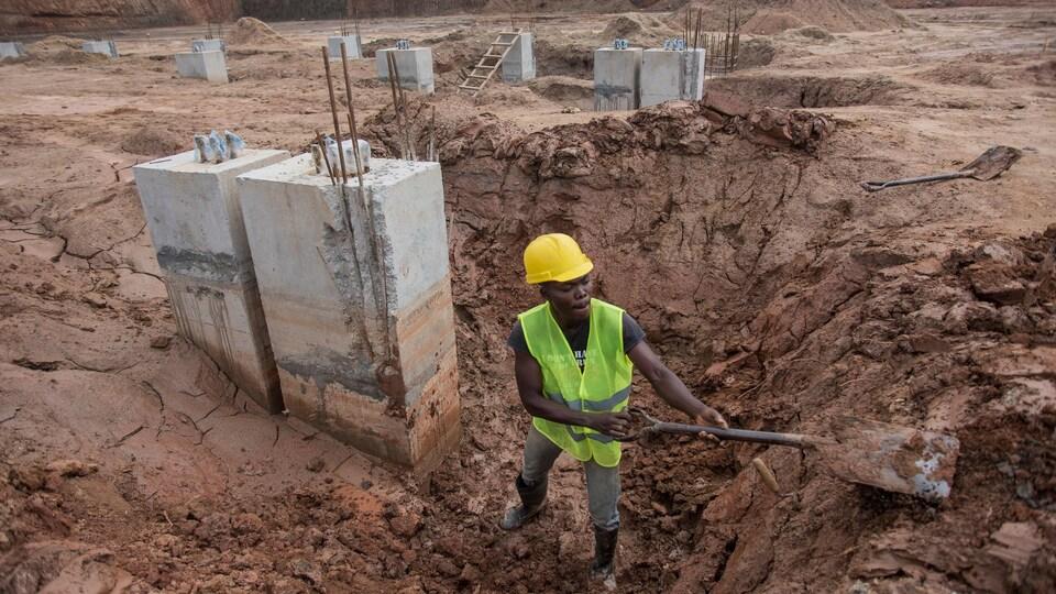 Un travailleur creuse avec une pelle dans un chantier de construction.