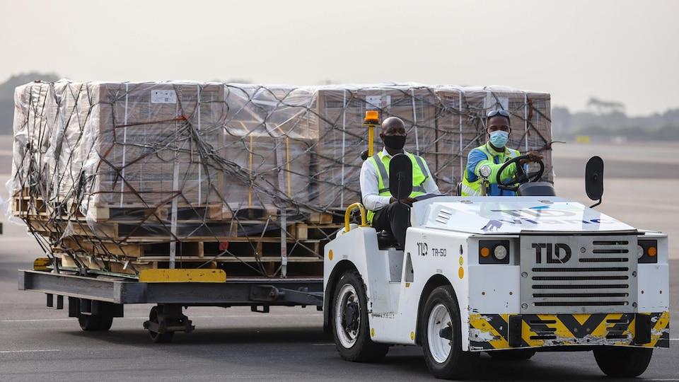 Deux hommes transportent des boites de doses de vaccins à bord d'un véhicule sur le tarmac de l'aéroport d'Accra.