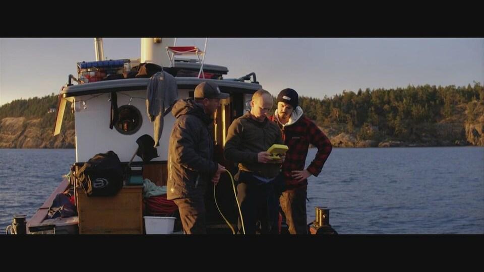 L'équipage de l'Emerald Sea Protection Society, debout sur un bateau. Ils regardent tous une télécommande.