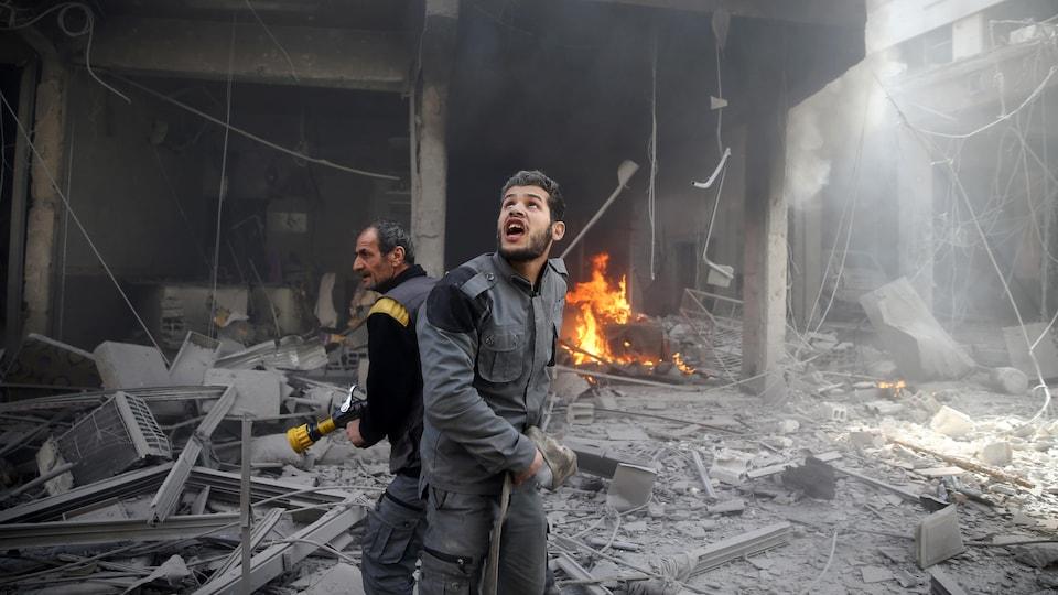 Un homme avec une hache regarde le ciel, alors qu'un autre tient une lance d'incendie, parmi les décombres.