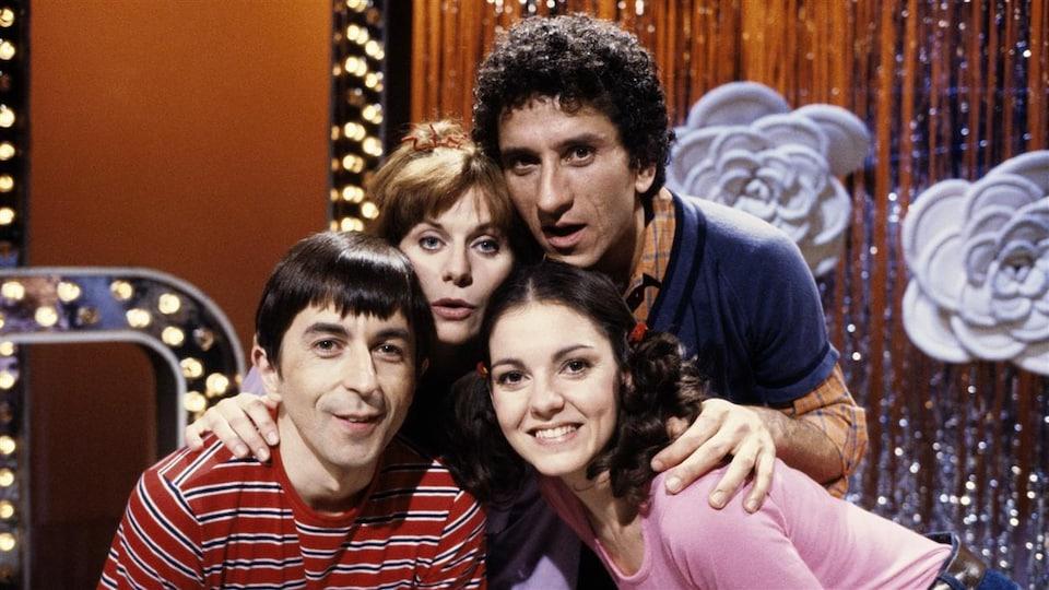 Ghyslain Tremblay et trois autres acteurs et actrices sourient devant un décor de studio.