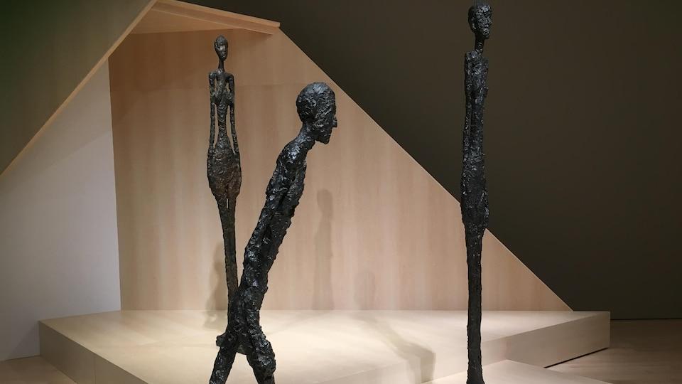 L'homme qui marche de Giacometti, 1960. Il s'agit d'une sculpture monumentale en bronze, On y aperçoit un homme filiforme.
