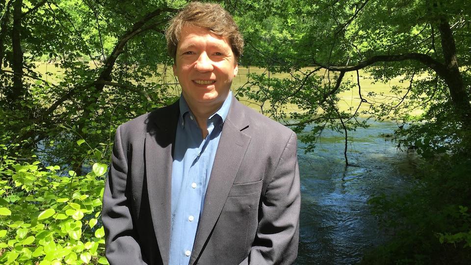Gil Rogers debout devant une rivière.
