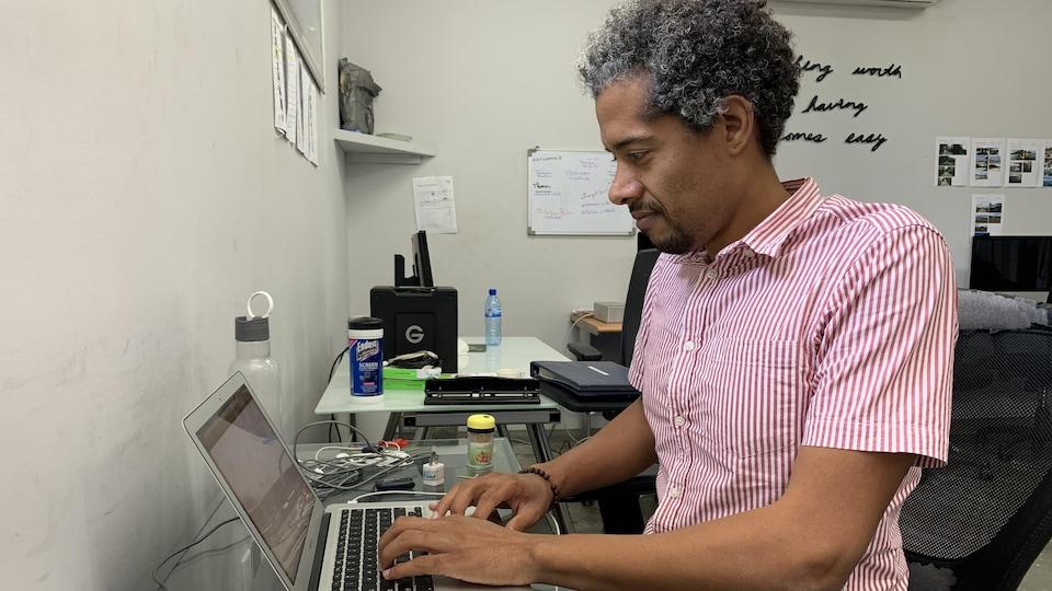 Gilbert Mirambeau travaille sur son ordinateur portable.