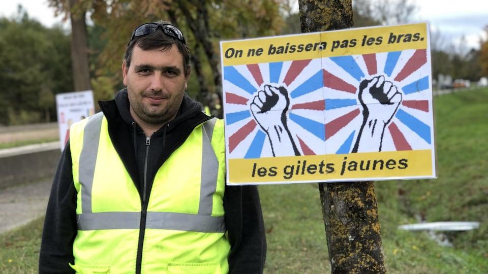 Manu sourit à la caméra. À côté de lui, une pancarte avec le slogan « On ne baissera pas les bras. Les gilets jaunes. »
