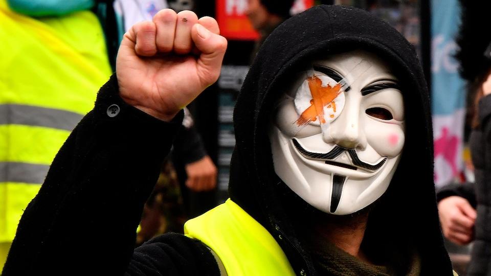 Un manifestant portant un gilet jaune, un masque d'Anonymous avec un bandeau sur l'œil droit brandit le poing.