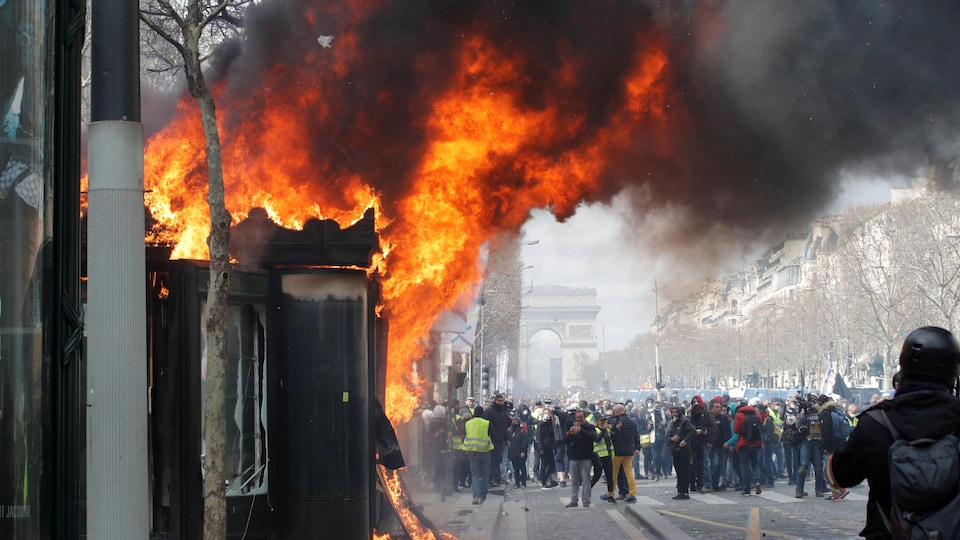 Un kiosque à journaux en feu aux abords des Champs-Élysées.