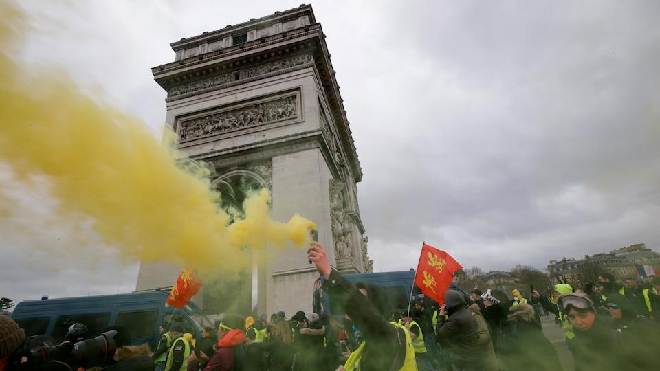 Des manifestants avec des fumigènes en main, au pied de l'Arc de triomphe.