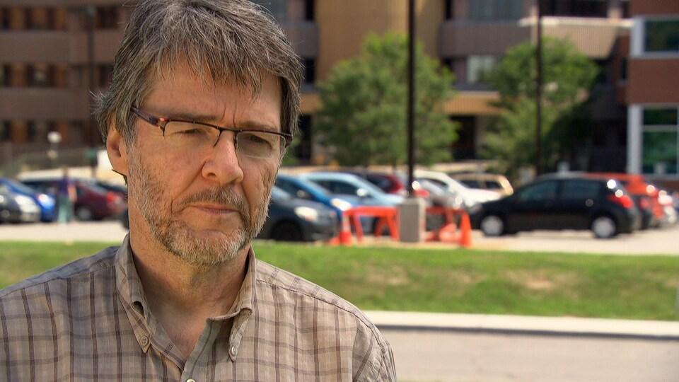 Gilles Aubé répond aux questions d'une journaliste devant l'Hôpital de Hull.