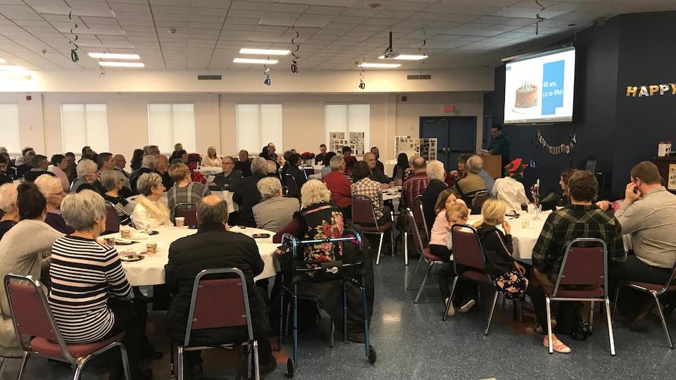 Des personnes assises autour des tables dans une salle.