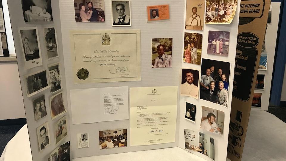 Des photos, des cartes ainsi que des lettres collées sur un carton pliant posé sur une table.