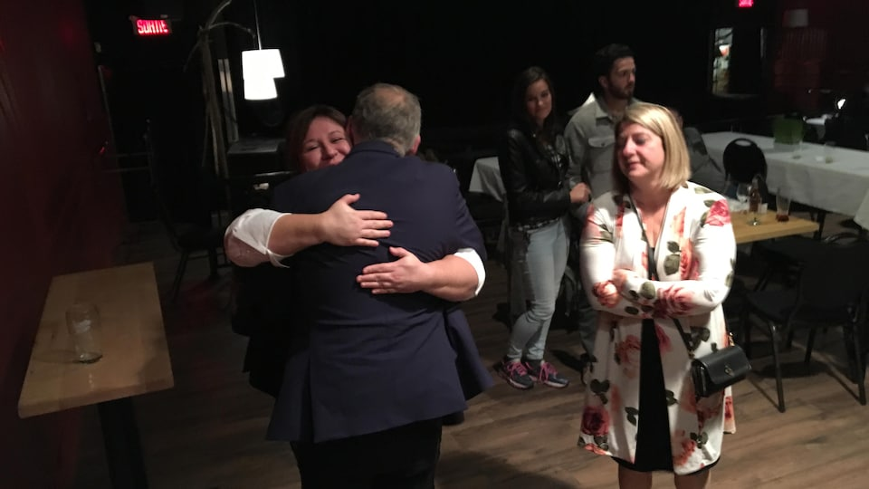 Un candidat serre dans ses bras une supporteur.