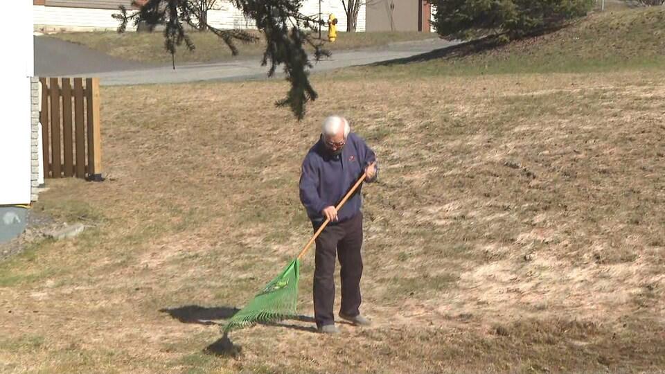 Un homme ratisse son terrain au printemps.