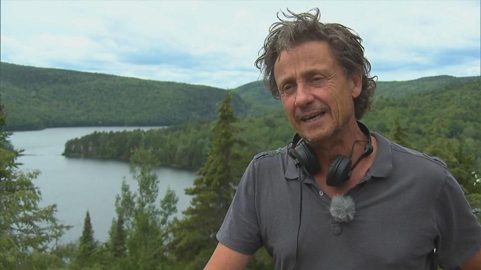 Un homme devant un lac et une forêt de conifères