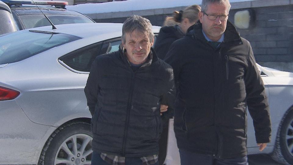 Gilles Guilbeault est menotté et escorté.