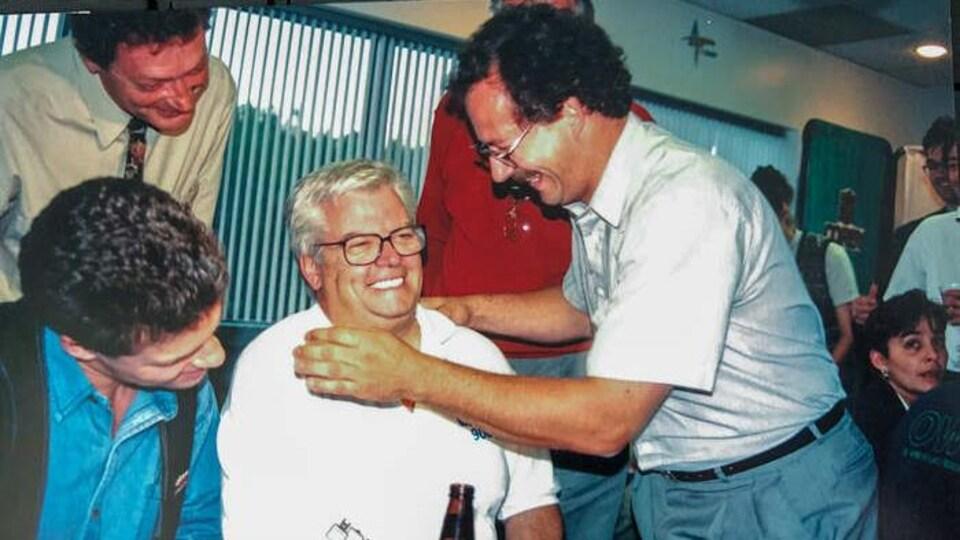 Des hommes sourient autour de Gilles et l'un d'entre eux a les bras autour de Gilles Hamel.