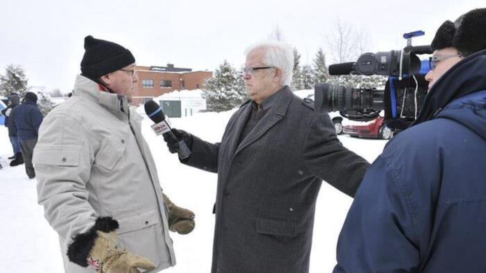 Gilles Hamel tend le micro vers un homme qui se fait filmer en même temps par un caméraman.