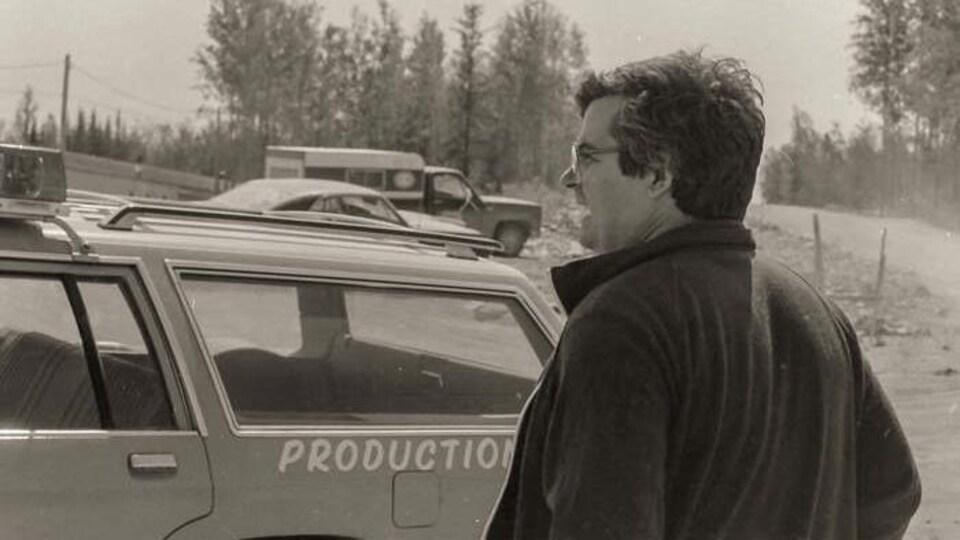 Photo en noir et blanc d'un homme devant une voiture de production.